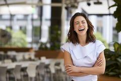 Śmiający się mieszającego biegowego młodego bizneswomanu z rękami krzyżować obrazy royalty free
