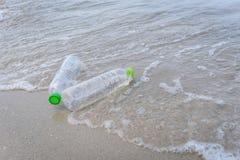 Śmieci w morzu z plastikową butelką na plażowym piaskowatym brudnym morzu na wyspie - problem związany z ochroną środowiska plast zdjęcia stock