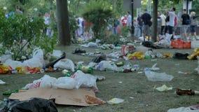 Śmieci, wliczając plastikowych paczek i butelek kłaść na trawie w parku, zaludnia odprowadzenie obok zdjęcie wideo