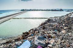 Śmieciarski usyp blisko ocean plaży pełno dym, ściółka, klingeryt butelki, banialuki i grat przy tropikalną wyspą, zdjęcie royalty free