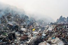 Śmieciarskiego usypu terenu widok pełno dym, ściółka, klingeryt butelki, banialuki i inny grat przy Thilafushi miejscowego wyspą, zdjęcie stock