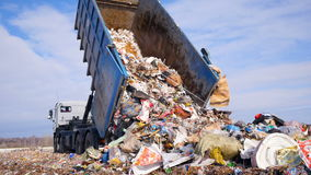 Śmieciarskiej ciężarówki disposed grat na wysypisku Pojazd odtransportowywa śmieci odpady