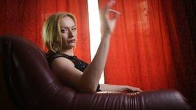 Śmiertelna kobieta w czarnej sukni i czerwonej pomadce na jej wargach siedzi w rzemiennym krześle i spojrzeniach w arrogantly zbiory