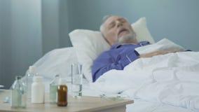 Śmiertelnie chory mężczyzna bierze środki przeciwbólowych i dosypianie w szpitalnym oddziale, cierpienie zbiory