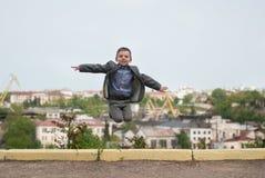 Śmieszna śliczna chłopiec w kurtki doskakiwaniu przeciw tłu port morski Zdjęcia Stock