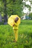 Śmieszna śliczna dziewczyna jest ubranym żółtego żakiet trzyma kolorowego parasol bawić się w ogródzie deszczu i słońca pogodą na obraz royalty free