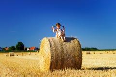 Śmieszna śliczna mała dziewczynka pozuje na haystack w lata polu Obrazy Royalty Free