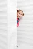 Śmieszna śliczna mała dziewczynka pozuje w białej scenerii Obraz Stock