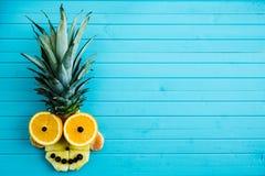 Śmieszna aplikacja od kawałków owoc na turkusowym drewnianym tle Owoc głowa robić ananas, pomarańcze, kopii przestrzeń Zdjęcia Royalty Free