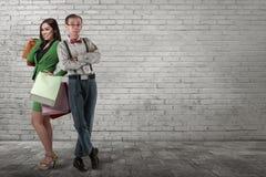 Śmieszna azjatykcia mężczyzna pozycja z zakupy kobietą trzyma papierową torbę Obrazy Royalty Free