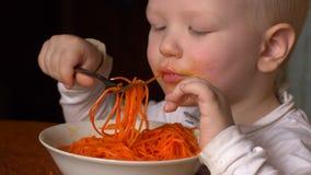 Śmieszna blond chłopiec je Koreańskiej marchwianej sałatki w kuchni obok jego brata Dzieci s? szcz??liwi wp?lnie zbiory