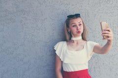 Śmieszna blondynka pozuje z smartphone obraz royalty free