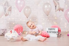Śmieszna brudna dziewczyna z, roztrzaskujący urodzinowy tort nad ścianą z cegieł i fotografia stock