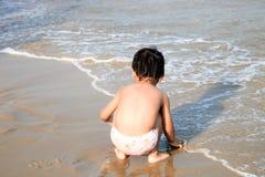 Śmieszna chłopiec bawić się na plaży Zdjęcie Royalty Free