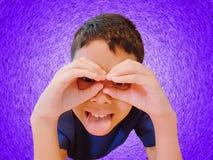 Śmieszna chłopiec Gestykuluje rękę i palce Nad oczami na Fiołkowym tle zdjęcie stock
