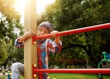 Śmieszna chłopiec na boisku Śliczna chłopiec sztuka outdoors, wspinaczka i na pogodnym letnim dniu fotografia stock