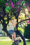 Śmieszna chłopiec na drzewie fotografia royalty free