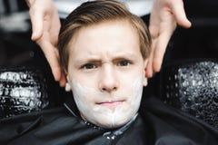 Śmieszna chłopiec w czarnym salonu przylądku w zakładzie fryzjerskim Fryzjer męski stosuje golenie pianę z pomocą golenia muśnięc zdjęcia royalty free