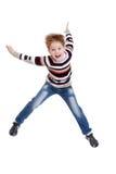Śmieszna chłopiec w pasiastej koszulce skacze z ona zdjęcia stock