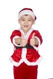 Śmieszna chłopiec w Santa kapeluszu pokazuje aprobaty, na lekkiego śniegu backgro Obraz Stock