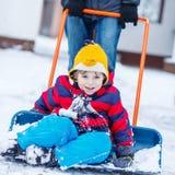 Śmieszna dzieciak chłopiec ma zabawę z jazdą na śnieżnej łopacie, outdoors Zdjęcie Stock