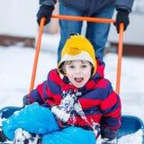 Śmieszna dzieciak chłopiec ma zabawę z jazdą na śnieżnej łopacie, outdoors Obrazy Stock