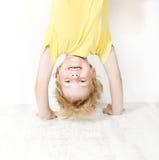 Śmieszna dziecka pozyci głowa nad piętą zdjęcia royalty free