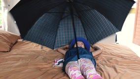 Śmieszna dziewczyna bawić się do domu z parasolem zbiory