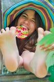 Śmieszna dziewczyna jest ubranym kolorowego kapelusz z lizakiem i pokazuje jej cieki w okno z gronowymi liśćmi Zdjęcia Royalty Free