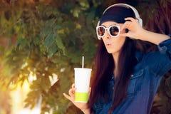 Śmieszna dziewczyna Jest ubranym okulary przeciwsłonecznych Pije sok i słuchanie muzyka w cajgu stroju obrazy royalty free