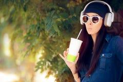 Śmieszna dziewczyna Jest ubranym okulary przeciwsłonecznych Pije sok i słuchanie muzyka w cajgu stroju fotografia royalty free