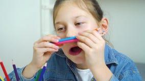 Śmieszna dziewczyna patrzeje kamerę i robi twarzom z barwionymi ołówkami jako wąs zdjęcie wideo