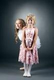 Śmieszna dziewczyna pozuje z jej nieśmiałą małą siostrą Obrazy Stock