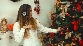 Śmieszna dziewczyna słucha muzyka z hełmofonami i dekoruje choinki zbiory wideo