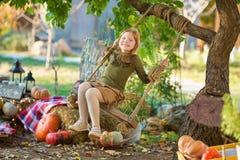 Śmieszna dziewczyna siedzi na huśtawkowym zachodzie w Halloween zieleni kostiumu bawić się plenerowy z strasznymi dźwigarek bania obrazy royalty free