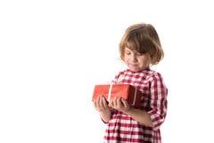 Śmieszna dziewczynka w czerwonej szkockiej kraty sukni z prezentem, pojęcie Wartościowościowy Fotografia Royalty Free