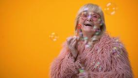 Śmieszna elegancka babcia w menchii round i żakieta okularach przeciwsłonecznych robi mydlanym bąblom, reklama zdjęcie wideo