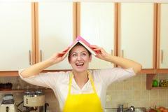 Śmieszna gospodyni domowa z książką kucharska na głowie Obrazy Stock