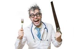 Śmieszna i szalona lekarka jest roześmianego i chwytów saw w ręce na whit Zdjęcia Stock