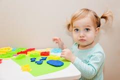 Śmieszna jeden roczniak dziewczyna bawić się z kolorowym ciastem lub daycare w domu Zdjęcie Royalty Free