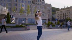Śmieszna młoda dziewczyna ma zabawy odprowadzenie wokoło tana i miasta kobieta słucha muzyka w dużych białych hełmofonach i zdjęcie wideo