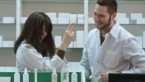 Śmieszna młoda farmaceuta ubierał w bielu munduru tanu przy apteką Zdjęcia Stock