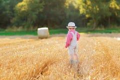 Śmieszna mała berbeć chłopiec w rzemiennych shors, chodzi przez whea zdjęcia royalty free