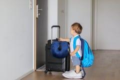 Śmieszna mała chłopiec w ojców butach z plecakiem, walizką i łyżką w jego ręce dużymi, zostaje w korytarzu patrzeje drzwiowego pr Fotografia Stock