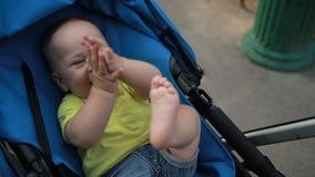 Śmieszna mała dziecięca chłopiec w wózku spacerowym w parku zdjęcie wideo
