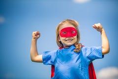 Śmieszna mała dziewczynka bawić się władza super bohatera fotografia royalty free