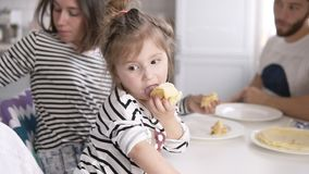 Śmieszna mała dziewczynka liże zgęszczonego mleko od blinu podczas gdy matka karmi kota Rodzinny śniadanie zbiory