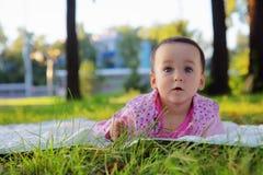 Śmieszna mała dziewczynka na trawie w lato parku obrazy stock