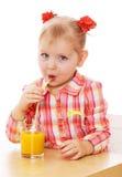 Śmieszna mała dziewczynka pije sok pomarańczowego obraz stock