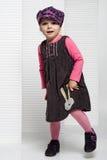 Śmieszna mała dziewczynka pozuje tanczyć w białej scenerii w modnym odziewa Obraz Stock
